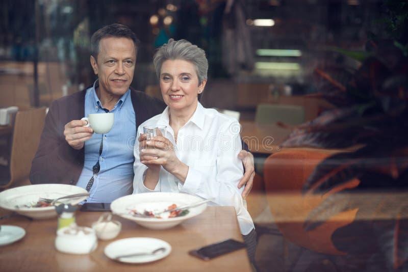愉快的典雅的年迈的夫妇会议在咖啡馆 免版税库存照片