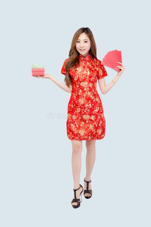 愉快的农历新年美丽的画象年轻亚裔在白色背景隔绝的妇女拿着红色礼物盒的和信封 免版税库存照片