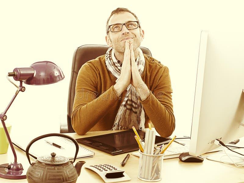 愉快的冥想的偶然企业家禅宗祈祷在书桌的,减速火箭的作用 免版税库存照片
