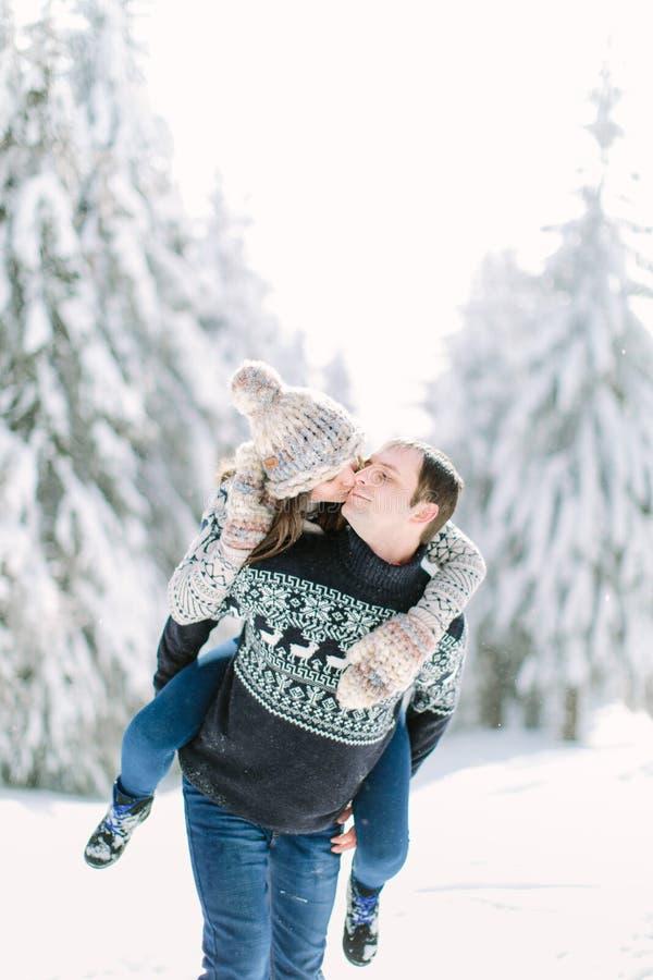 愉快的冬天旅行夫妇 给妇女肩扛乘驾的人冬天假期在多雪的森林里 免版税图库摄影