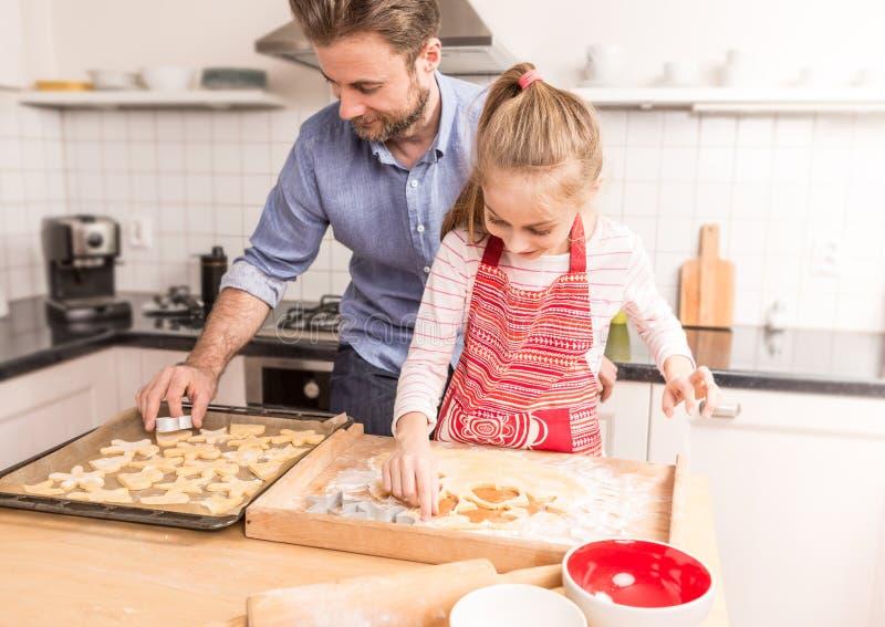 愉快的准备曲奇饼的父亲和女儿烘烤在kitch 库存图片