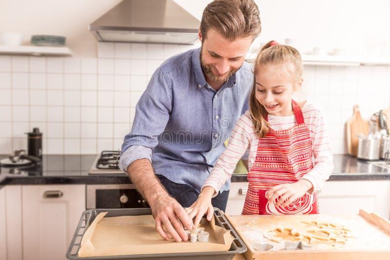 愉快的准备曲奇饼的父亲和女儿烘烤在kitch 免版税库存图片