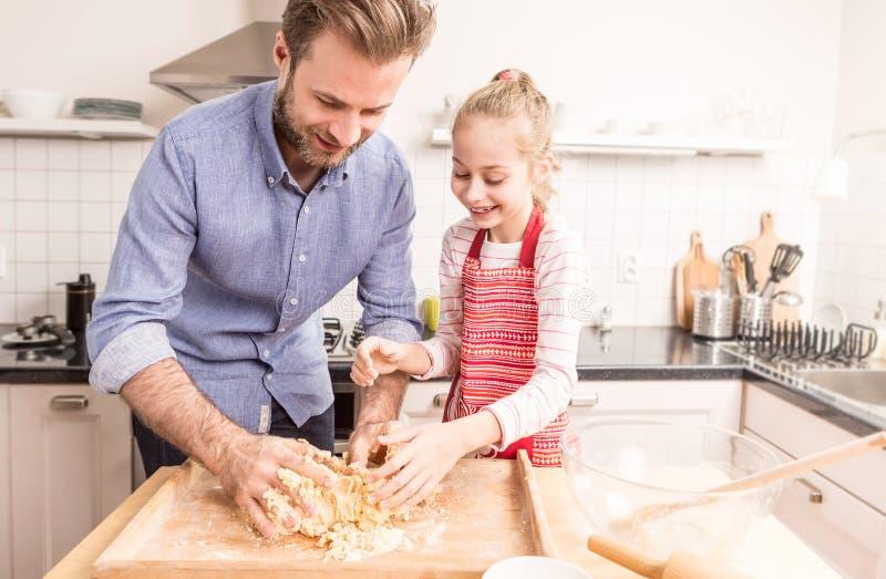 愉快的准备曲奇饼面团的父亲和女儿在厨房里 免版税库存照片