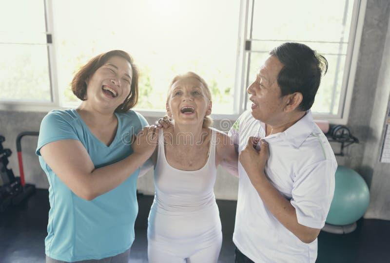 愉快的前辈的小组朋友瑜伽健身房的微笑和 年长 库存照片