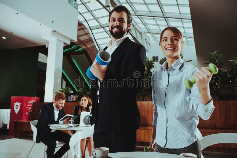 愉快的办公室工作者与哑铃一起使用 免版税库存照片