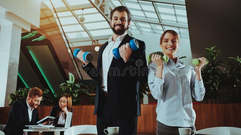愉快的办公室工作者与哑铃一起使用 免版税图库摄影