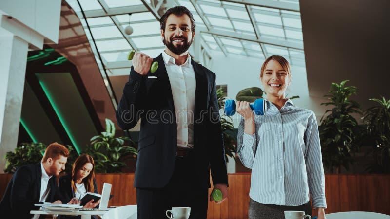 愉快的办公室工作者与哑铃一起使用 图库摄影