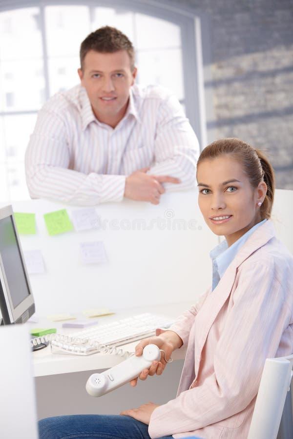 愉快的办公室微笑的工作者 免版税图库摄影