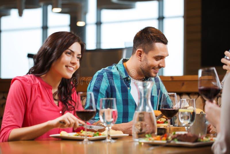 愉快的加上吃在餐馆的朋友 免版税库存图片