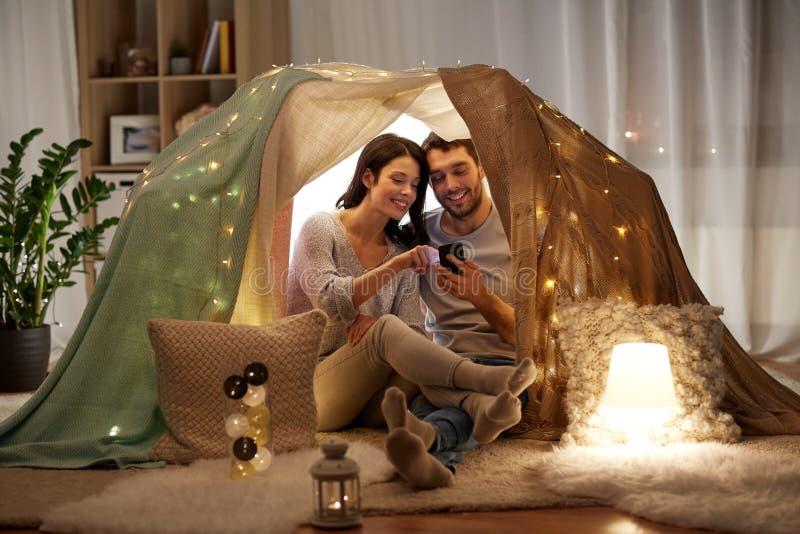 愉快的加上在孩子帐篷的智能手机在家 免版税库存图片