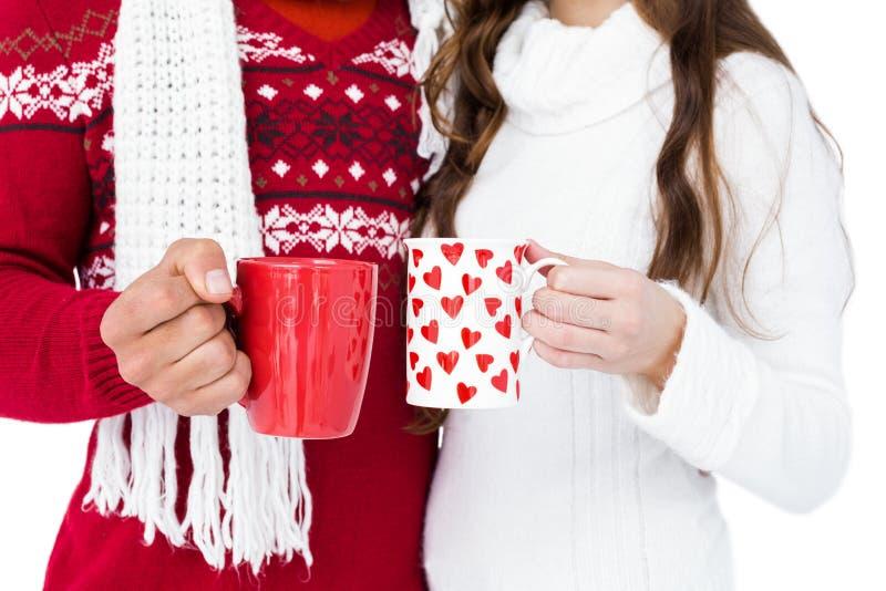 愉快的加上拿着杯子的圣诞老人帽子 免版税库存照片