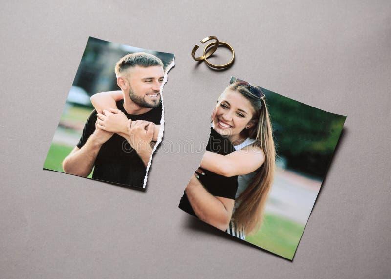 愉快的加上被撕毁的照片在灰色背景的圆环 离婚的概念 库存照片