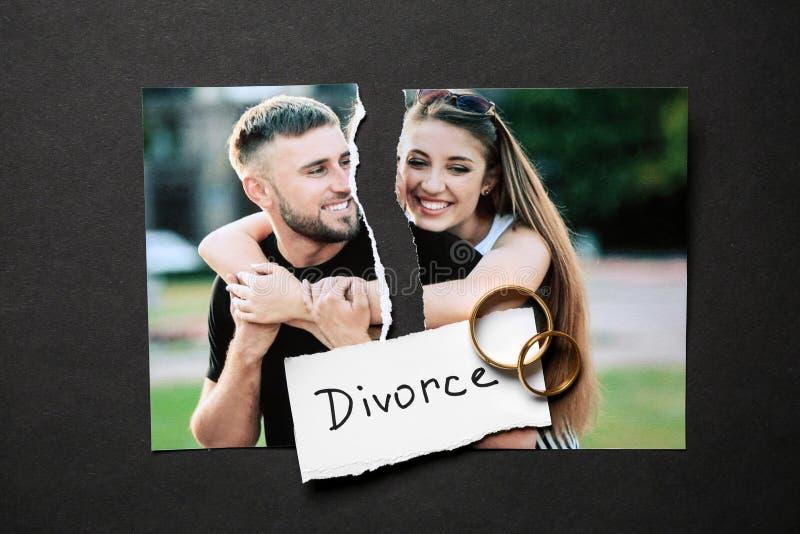 愉快的加上被撕毁的照片在黑暗的背景的圆环 离婚的概念 库存图片