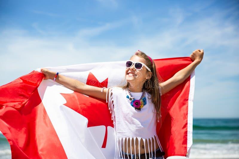 愉快的加拿大女孩举着加拿大的振翼的白色红旗反对天空蔚蓝和海洋背景 免版税库存照片