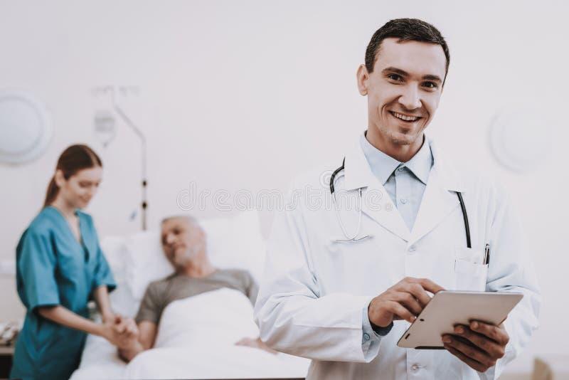 愉快的医生和护士 患者在轻便小床说谎 免版税库存图片