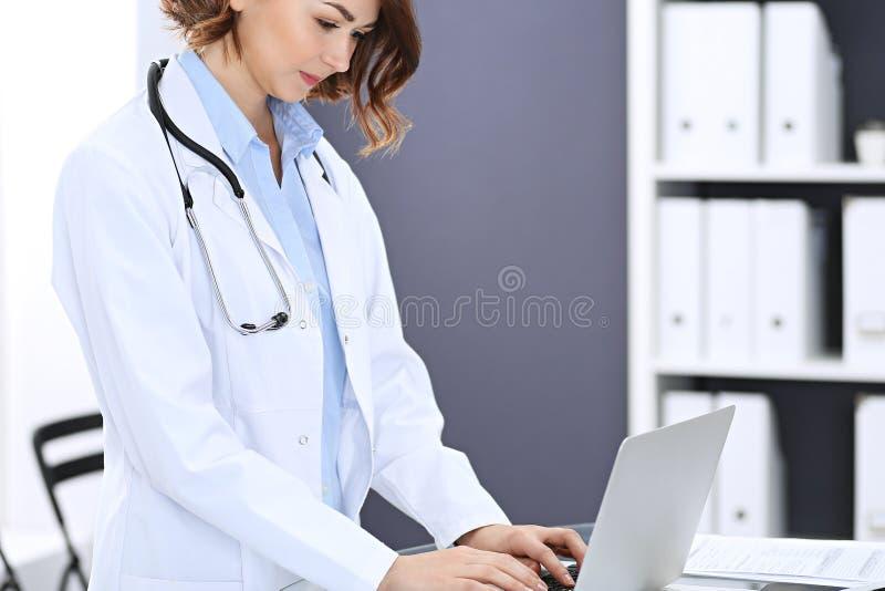 愉快的医生妇女在工作 使用便携式计算机的女性医师画象,当站立近的总台在时 库存照片