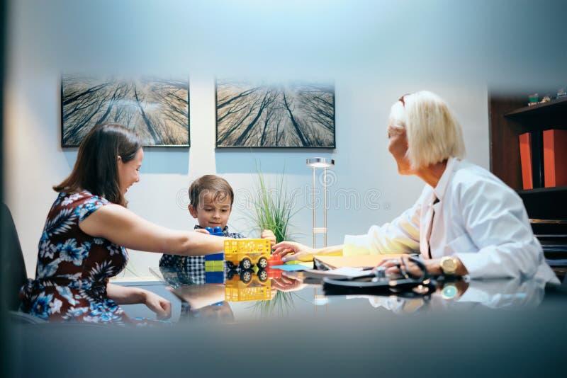 愉快的医生有妈妈和男孩的Woman Working和使用 免版税库存图片