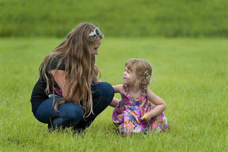 愉快的十几岁的女孩和草的一个小孩 库存照片