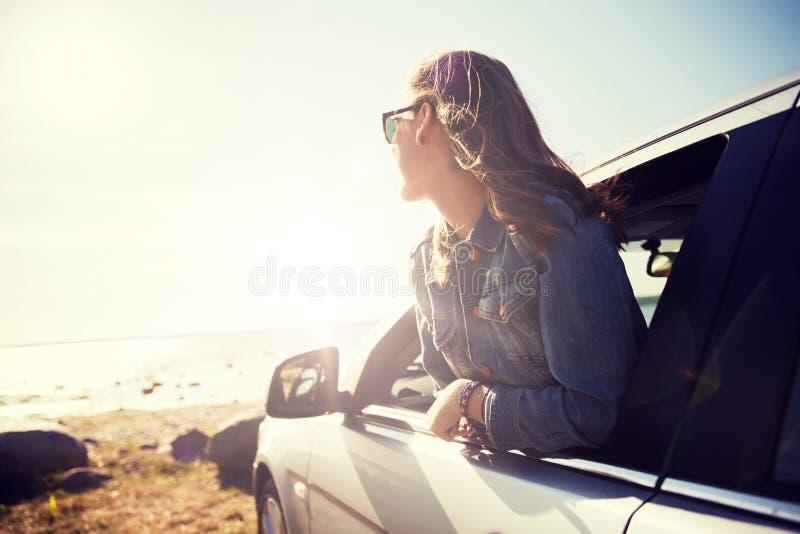 愉快的十几岁的女孩或少妇汽车的 免版税库存照片
