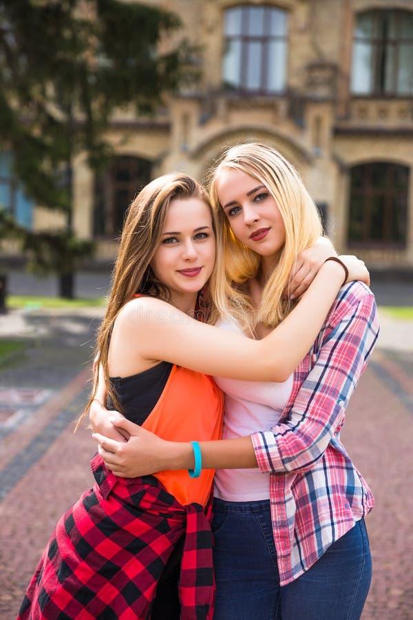年轻愉快的十几岁的女孩获得乐趣在城市公园 好夏天天气 走在公园的女朋友 免版税库存照片