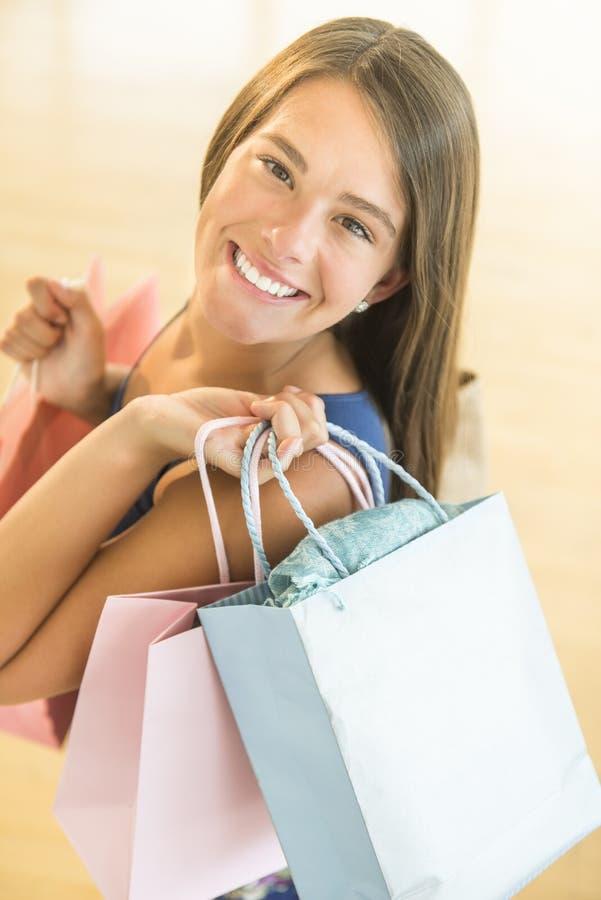 愉快的十几岁的女孩运载的购物袋 免版税库存照片