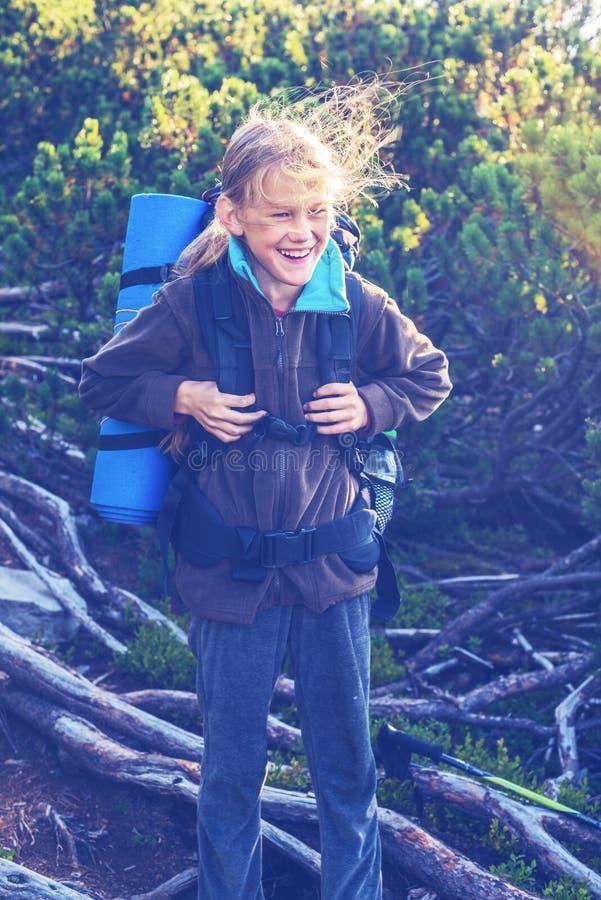 愉快的十几岁的女孩,有飞行头发的,在山坡 库存图片