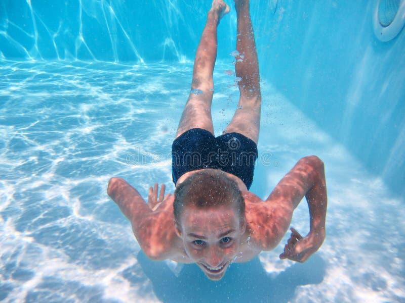 愉快的十几岁的男孩在水池潜水 免版税图库摄影
