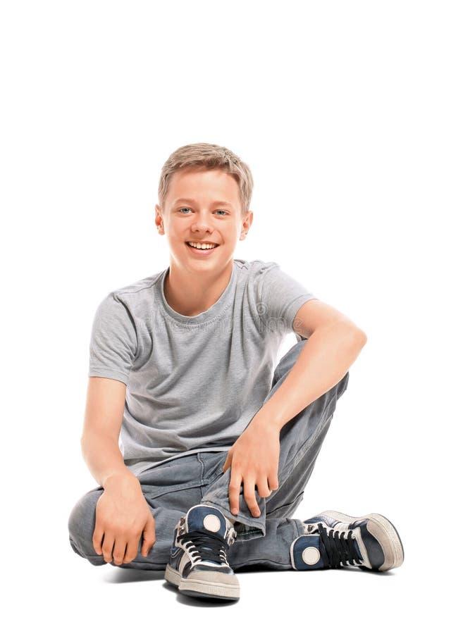 愉快的十几岁的男孩坐地板 库存图片