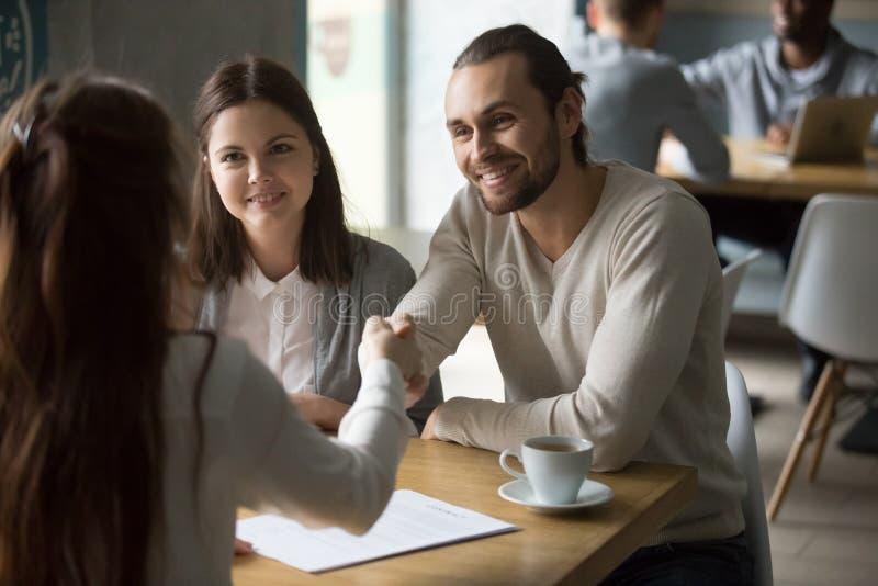 愉快的千福年的夫妇握手在签字以后信任经纪 免版税库存图片