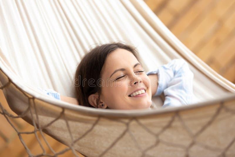 愉快的千福年的女孩放松在吊床外面 免版税图库摄影