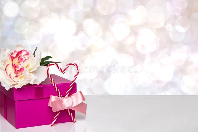 愉快的华伦泰或母亲节背景 有一束美丽的白花的红色与弓丝带的礼物盒和红心在桌上 图库摄影