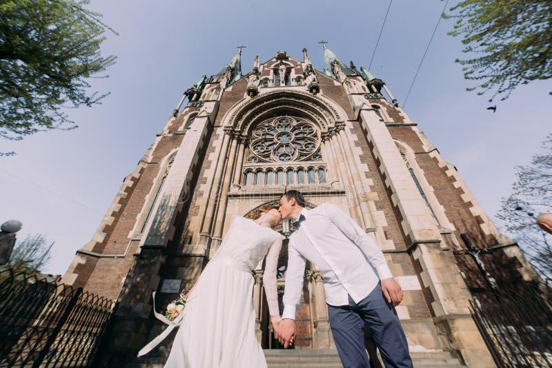 愉快的华美的亲吻在惊人的大厦教会背景的新娘和时髦的英俊的新郎在城市 免版税库存照片
