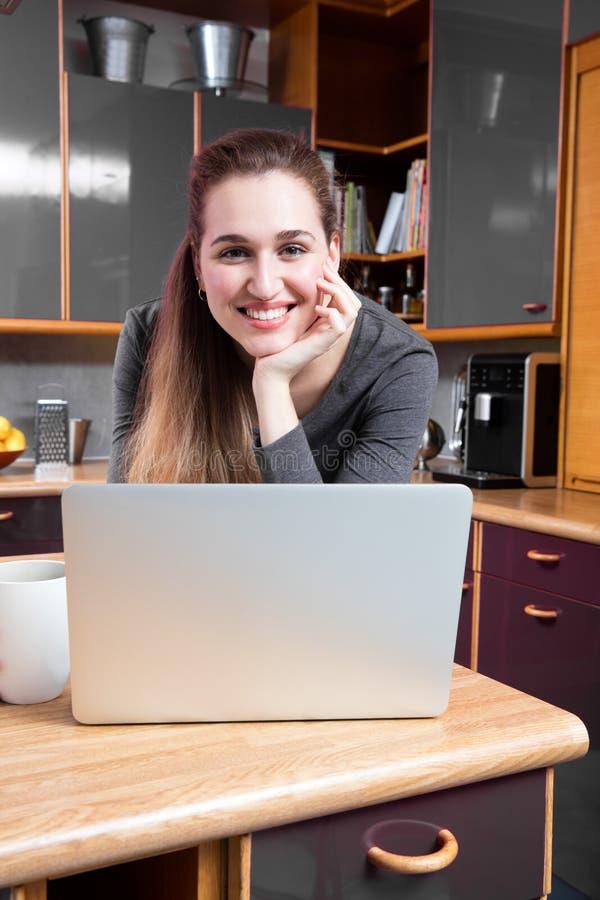 愉快的华美的少妇在她的使用她的计算机的厨房里 库存照片