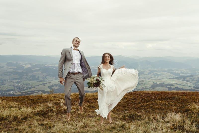 愉快的华美的获得新娘和时髦的新郎跳跃和乐趣, b 免版税库存照片