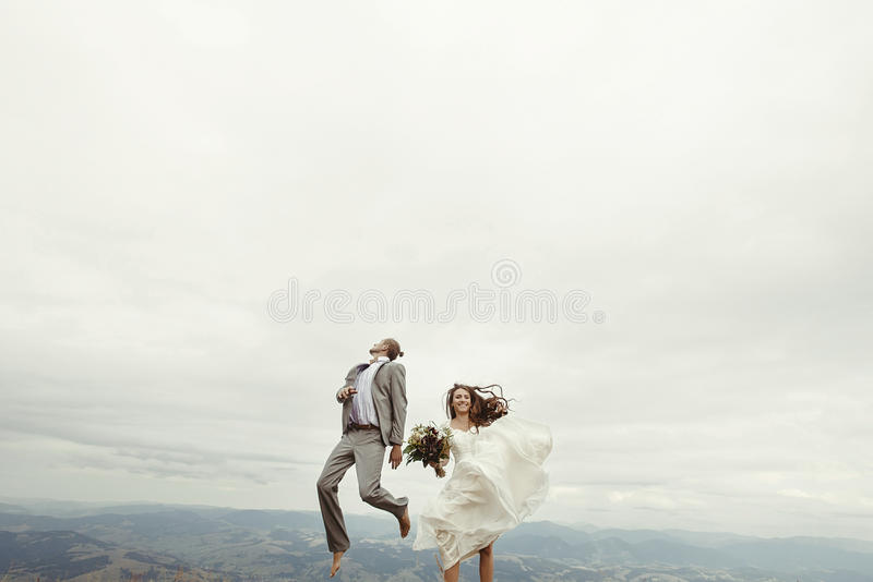 愉快的华美的获得新娘和时髦的新郎跳跃和乐趣, b 图库摄影