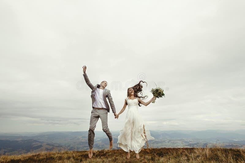 愉快的华美的获得新娘和时髦的新郎跳跃和乐趣, b 库存图片