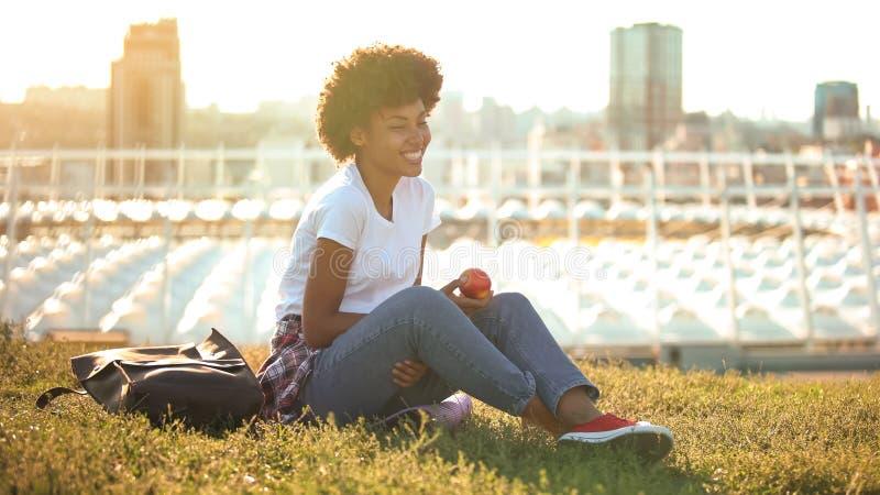 愉快的卷发的女性举行的苹果和坐绿色草坪,健康饮食 库存图片
