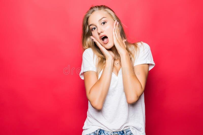 愉快的叫喊的惊奇的年轻女人身分画象被隔绝在红色背景 免版税库存照片
