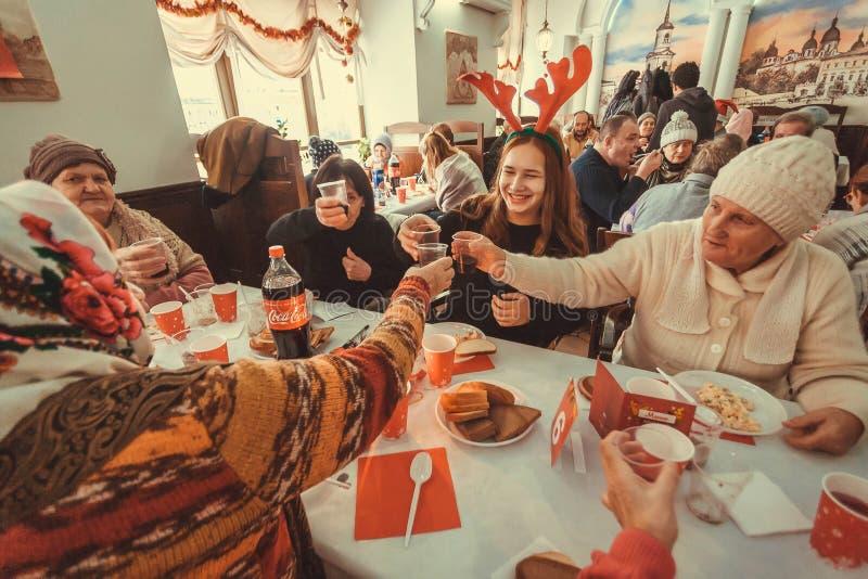 愉快的可怜的人民庆祝假日和饮用食物在圣诞节无家可归者的慈善晚餐 免版税图库摄影