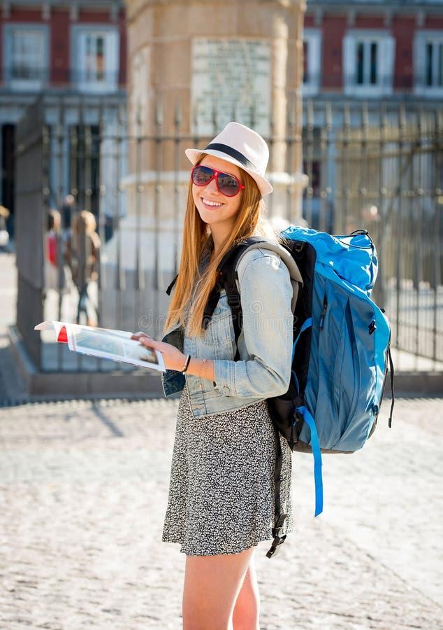 愉快的可爱的交换学生女孩获得乐趣在参观马德里市读书游人指南的镇里 图库摄影