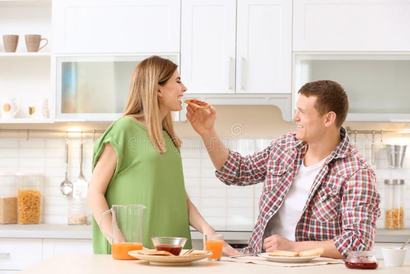 愉快的可爱的夫妇食用早餐用鲜美面包在桌上在厨房 免版税库存照片
