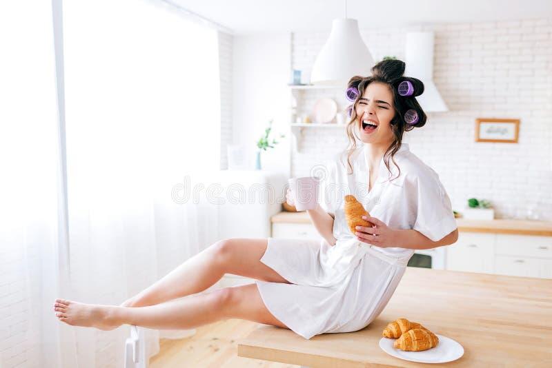 愉快的可爱的好年轻管家坐桌在厨房里 大声笑  在手上拿着白色杯子 ?? 图库摄影