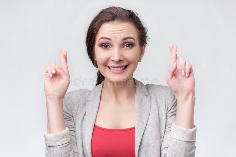 愉快的可爱的年轻女人保留手指横渡了祝愿爆发 免版税库存图片