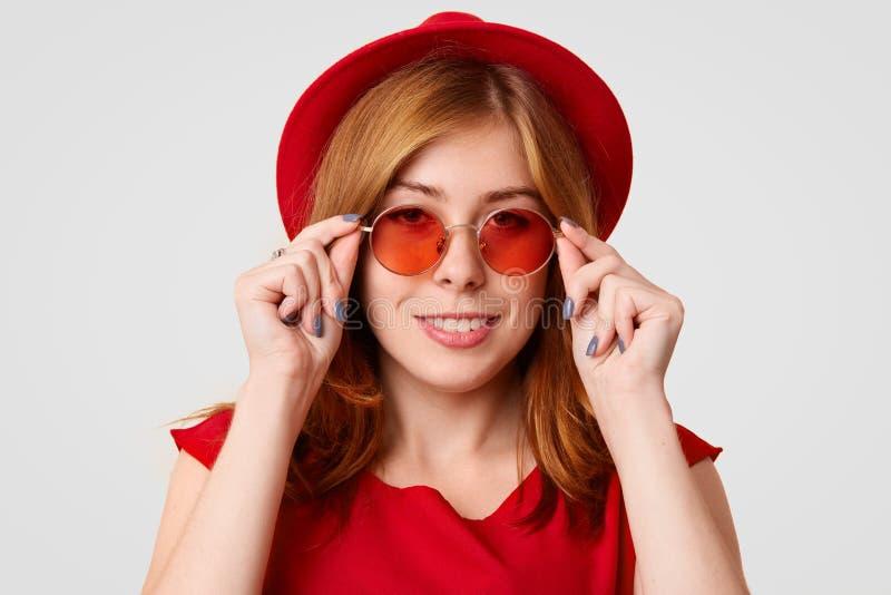 愉快的可爱的年轻女性模型在演播室,佩带红色树荫,帽子,并且女衬衫,有她自己的样式,看起来典雅,保留在外缘的手 免版税库存图片