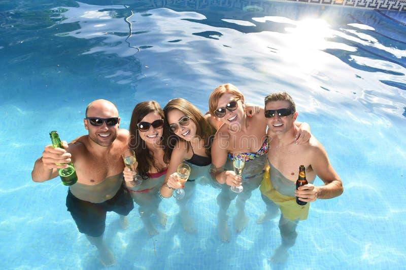 愉快的可爱的男人和妇女比基尼泳装的有浴在旅馆手段游泳池饮用的啤酒 免版税库存照片