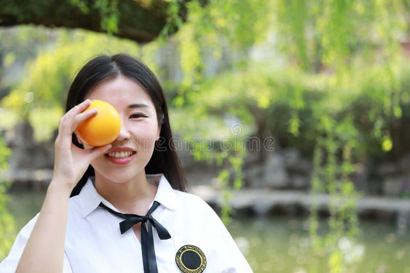 愉快的可爱的秀丽亚洲中国高中女学生微笑在一个公园庭院春天夏天享受业余时间吃果子桔子 库存图片