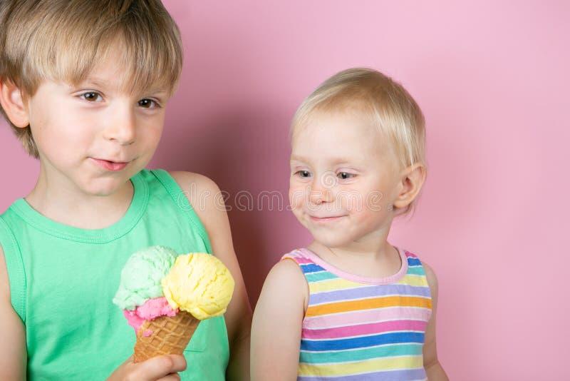 愉快的吃在桃红色bakground前面的男孩和女孩冰淇淋 库存图片