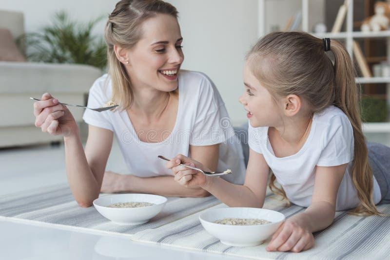 愉快的吃谷物膳食的母亲和女儿,当说谎时 库存照片