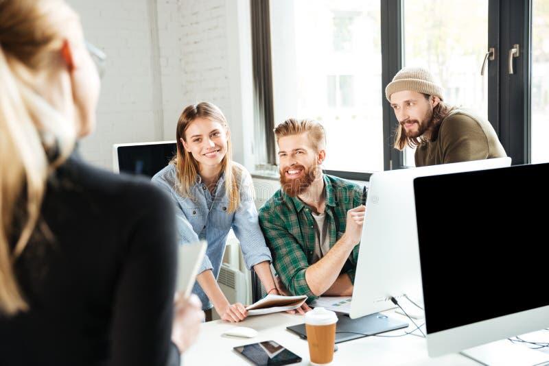 愉快的同事在办公室谈话互相 免版税图库摄影