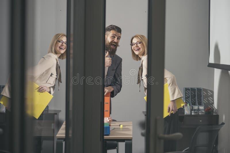 愉快的同事看有玻璃墙的现代办公室 企业夫妇微笑在会议上 有胡子的男人和性感的妇女 免版税库存照片